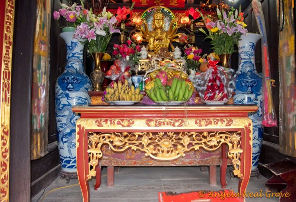Altar in Temple in Hanoi piled with offerings during Tet celebration
