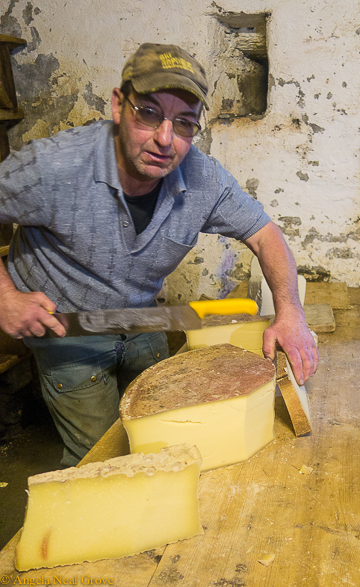 Mont Blanc challenge: cutting thick slices of world famous Beaufort cheese for a picnic lunch