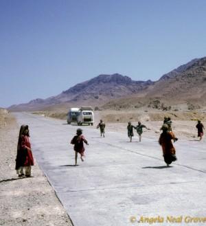 Kochi children running after a van on the Herat-Kandahar Road