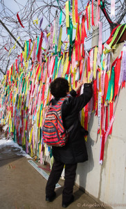 South Korea woman pins a message on the fence at the DMZ. There is no contact for families divided between South and North Korea Photo: Angela Neal Grove