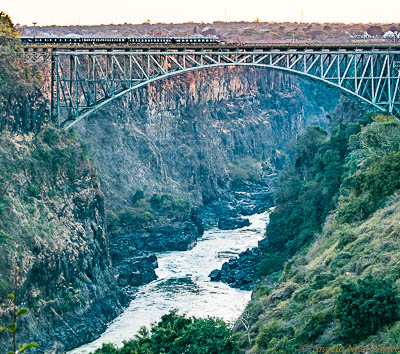 Victoria Falls Smoke That Thunders; Victoria Falls Bridge spans the Zambezi River which is the border between Zambia and Zimbabwe. It is a favorite for bungee jumpers