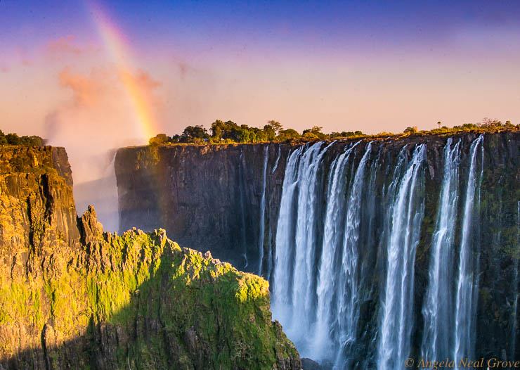 Victoria Falls Smoke That Thunders: Rainbow over Victoria Falls at sunrise.