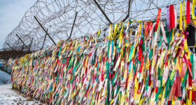 Korea's DMZ Through My Lens: Double chain-link fence topped with razor wire coils at the border. On it are pinned thousands of wishes and messages for peace and reunification placed by South Korean citizens, some of whom have family beyond the border.