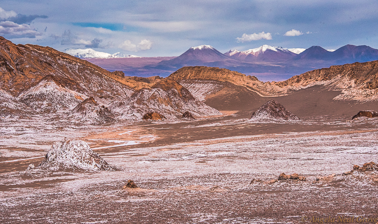 Otherworldly Atacama Desert.  Valley of Mars, Atacama has rugged rocky formations which give an other-worldly Mars-like look to this valley. The white frosting is salt. In the background is the chain of volcanoes on the border of Bolivia. PHOTO; ANGROVE